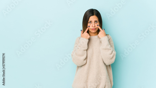 Young woman isolated on blue background crying, unhappy with something, agony and confusion concept Fototapet