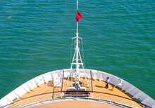 View Over Bow With Red Flag Of Luxury Cruiseship Or Cruise Ship Liner On Green Sea Or Ocean With Crew Member Looking Up