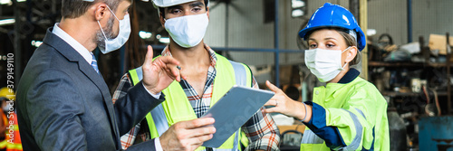 Obraz Industrial engineers and businessman in suite and safety helmet wearing mask working in factory, planning, discussing and training workers with tablet in metalwork place , teamwork and team concept - fototapety do salonu