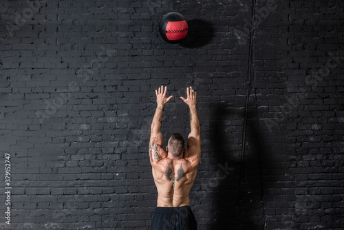 Vászonkép Young strong sweaty focused fit muscular man with big muscles doing throwing med