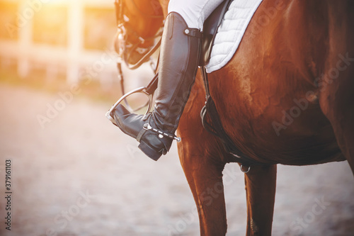 The foot of the rider sitting on the horse is dressed in a black boot with a spur and rests on a metal stirrup, illuminated by sunlight. Horseback riding. Equestrian sport.