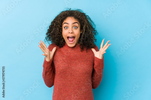 Fototapeta Young african american curly hair woman celebrating a victory or success, he is surprised and shocked. obraz