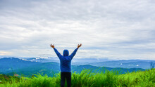 A Happy Traveler, Standing On The Grass, Admiring The Beautiful Mountain Scenery. People Enjoy Nature Back View