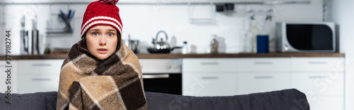 Fotografia horizontal concept of cold woman in warm hat, wrapping in warm plaid blanket whi