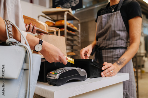 Photo Paying with her credit card in a bakery shop, making a purchaise