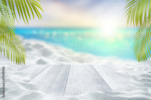 Fototapeta Top of white wood table and white sand dunes with blurred sea and palm leaves as frame beach in summer Concept obraz