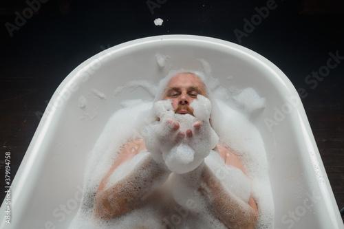 Top view of a bald man with a red beard splashing in the foam bath Wallpaper Mural