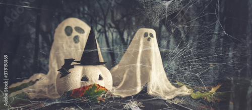 Fototapeta Happy halloween holiday. Halloween decorations, black and white pumpkins mask coronavirus,bats, ghosts black background. Halloween party greeting card mockup with copy space. Halloween greeting banner obraz