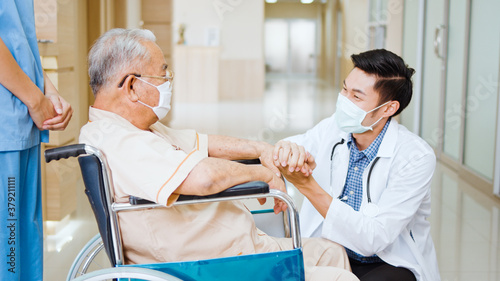 Young male Asian doctor crouch down holding hand and talk to the senior adult patient on wheelchair in hospital hallway. Medical healthcare job, or hospital business concept