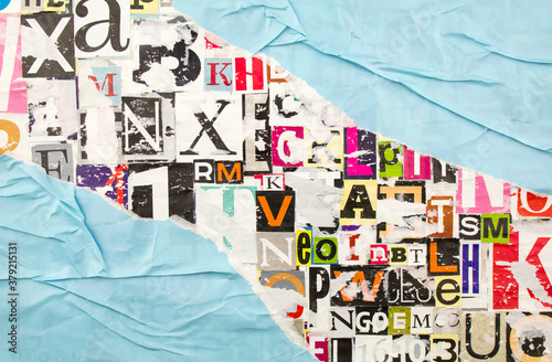 Torn, ripped and crumpled blue paper on colorful abstract collage from clippings with letters and numbers background Fototapet