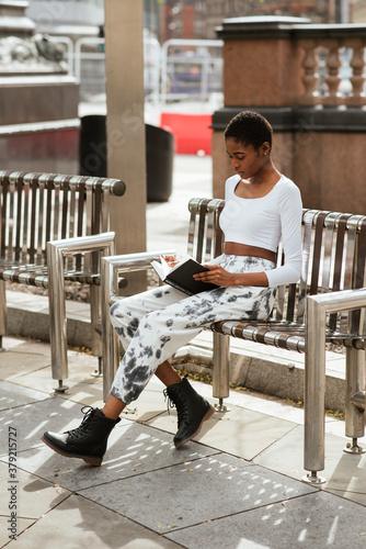 Tela Vertical shot of an African-American woman holding a book