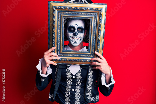Young man wearing mexican day of the dead costume holding empty frame looking po Canvas Print