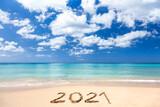 Fototapeta Wieża Eiffla - 2021 written on sandy beach