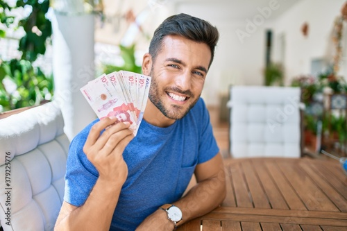 Fotografie, Tablou Young hispanic man smiling happy holding colombian pesos banknotes at the terrace