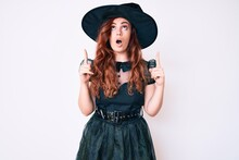 Young Beautiful Woman Wearing Witch Halloween Costume Amazed And Surprised Looking Up And Pointing With Fingers And Raised Arms.