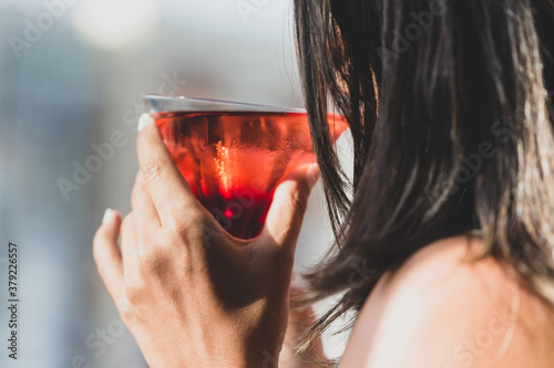 Unrecognizable brunette woman drinking cocktail at the bar, happy hour concept