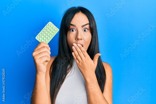 Valokuva Young beautiful hispanic girl holding birth control pills covering mouth with hand, shocked and afraid for mistake
