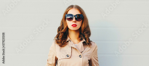 Fototapeta Close up portrait of attractive woman wearing a coat, sunglasses in the city over gray background obraz
