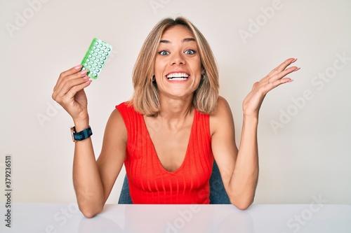 Fototapeta Beautiful caucasian woman holding birth control pills celebrating victory with h