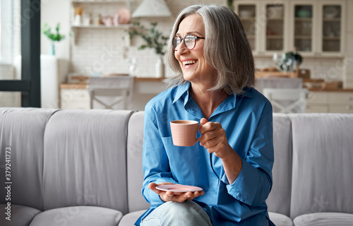 Fotografía Happy beautiful relaxed mature older adult grey-haired woman drinking coffee relaxing on sofa at home