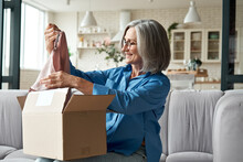 Happy Middle Aged Woman Buyer Opening Parcel Box At Home. Smiling Old Mature Female Customer Shopper Receiving Online Shop Purchase Buying Clothes Unpacking Delivery Postal Shipping Package On Couch.