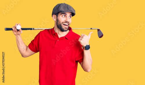Photo Young handsome man with beard playing golf holding club and ball pointing thumb