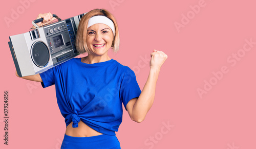 Fotografía Young blonde woman wearing sportswear holding boombox, listening to music scream