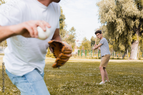 Fotografia, Obraz selective focus of teenager son with softball bat looking at father while playin
