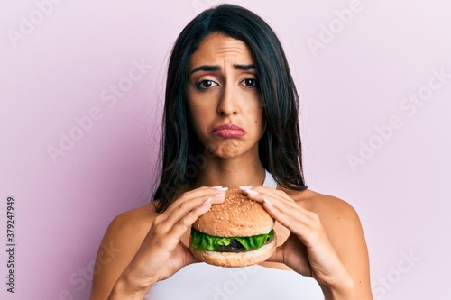 Fototapeta Beautiful hispanic woman eating a tasty classic burger depressed and worry for distress, crying angry and afraid. sad expression. obraz