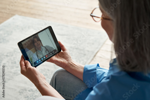 Slika na platnu Over shoulder closeup view of old woman patient video calling virtual doctor using tablet at home
