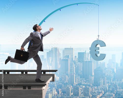 Obraz na plátne Businessman chasing money on fishing rod
