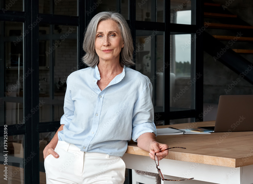 Fototapeta Confident stylish european mature middle aged woman standing at workplace. Stylish older senior businesswoman, 60s gray-haired lady executive leader manager looking at camera in office, portrait.