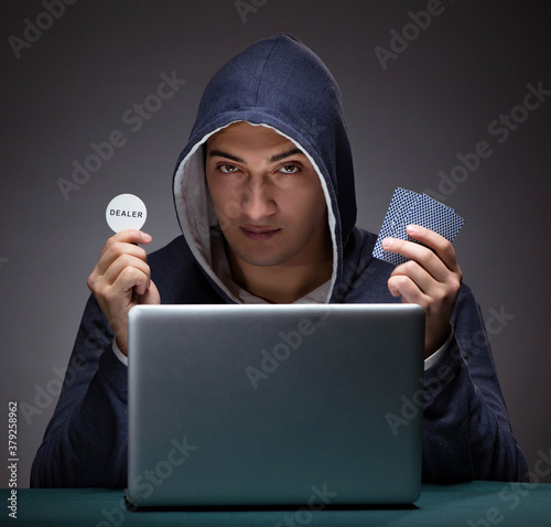 Tela Young man wearing a hoodie sitting in front of a laptop computer
