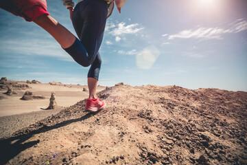 Fitness woman trail runner cross country running on sand desert