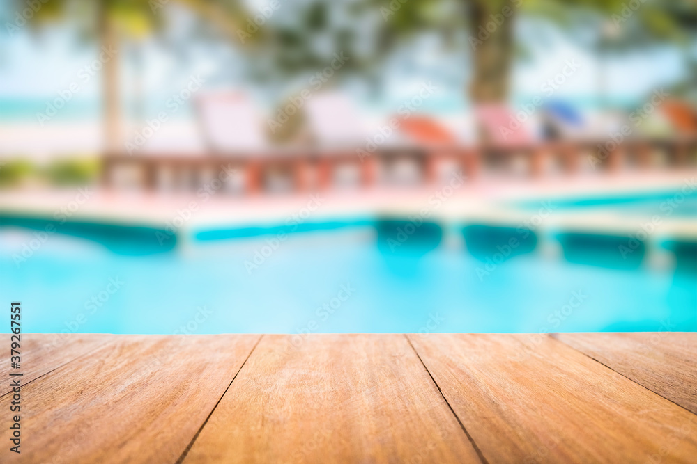 Fototapeta Image of wood table in front of a swimming pool blurred background. Brown wooden desk empty counter in front of the poolside on beautiful beach resort and outdoor spa.