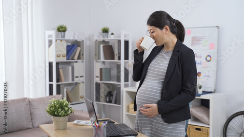 elegant asian chinese pregnant ceo woman standing in the office is drinking tea Canvas Print
