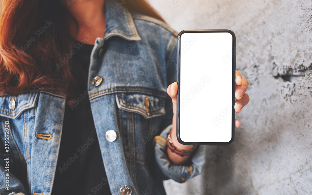 Fototapeta Mockup image of a woman holding and showing a mobile phone with blank white screen