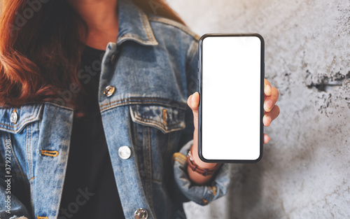 Fototapeta Mockup image of a woman holding and showing a mobile phone with blank white scre