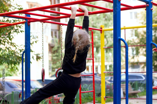 Photo Blond toddler girl with pigtails hanging on a horizontal bar on the playground on the warm day