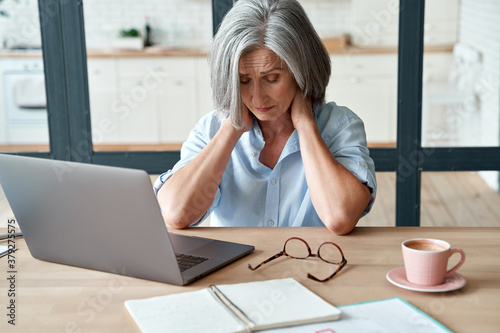 Fotografia Tired stressed old mature business woman suffering from neckpain working from home office sitting at table
