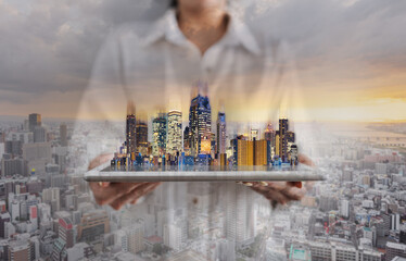 Real estate business and building technology. Double exposure businesswoman holding digital tablet with building hologram and city sunrise background