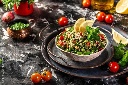 Fototapeta Tabbouleh salad. Middle eastern or arab dish. Levantine vegetarian salad with parsley, mint, bulgur, tomato. Vegan food. Top view obraz