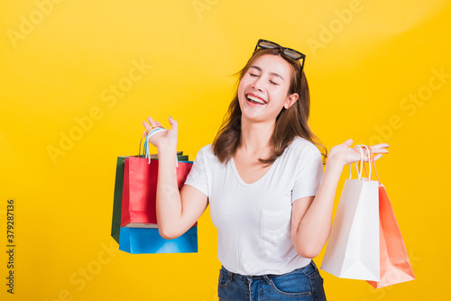 Fototapeta Asian Thai portrait happy beautiful cute young woman smiling stand with sunglasses excited holding shopping bags multi color close eyes, studio shot isolated yellow background with copy space obraz