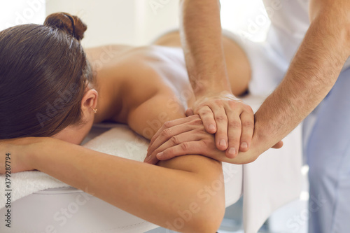 Relaxed woman getting medical body massage done by professional physiotherapist in modern clinic