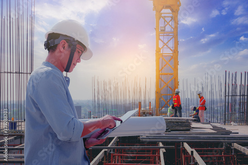 Fototapeta Smart civil architect engineer inspecting and working outdoors structure building site with blueprints. engineering and architecture concept. obraz