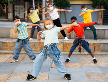 Girls And Boys Hip Hop Dancers In Protective Face Masks Doing Dance Workout During Open Air Group Class, Keeping Social Distance