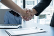 Friendly businessmen and executives shake hands after successful agreement with employment contracts, recruitment, and employment concepts