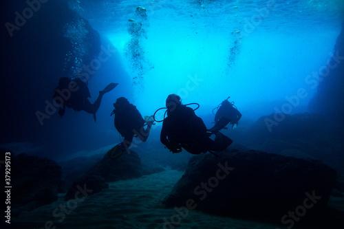 Fotografija Scuba divers black silhouettes in a blue cave making bubbles