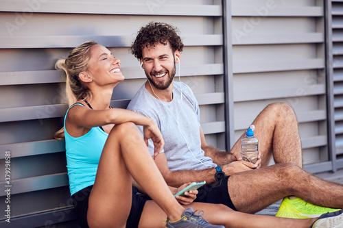 Fotografie, Obraz Modern urban couple making pause on the sidewalk during jogging / exercise