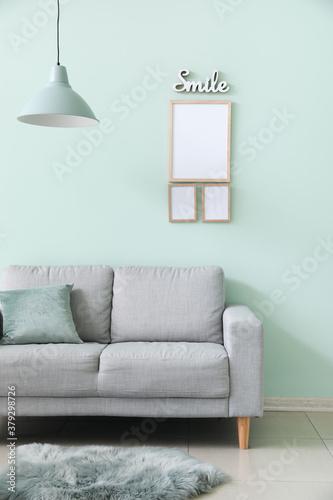 Fototapeta Interior of modern room with sofa and blank frames obraz